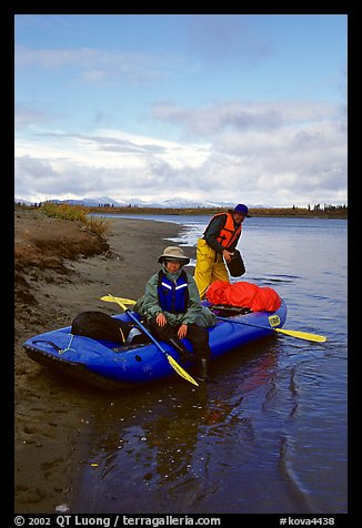 Canoeists finish  loading  with the boat prior to launching. Kobuk Valley National Park, Alaska (color)