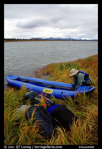 Canoeist unloading the canoe on a grassy riverbank. Kobuk Valley National Park, Alaska (color)