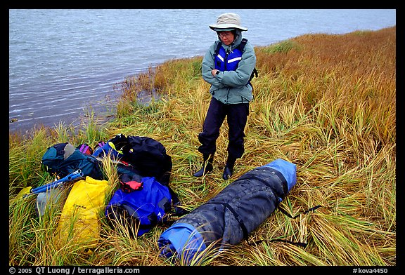 Canoeist standing next to gear and deflated and folded  canoe. Kobuk Valley National Park, Alaska (color)
