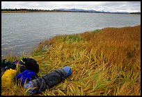 Gear and folded  canoe on a grassy riverbank of the Kobuk River. Kobuk Valley National Park, Alaska