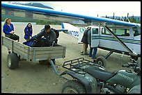 Unloading the gear from the plane to a trailer on the Port Alsworth airstrip. Lake Clark National Park, Alaska (color)
