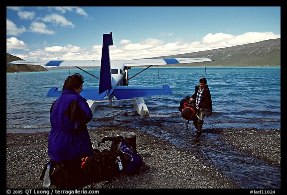 Pilot unloading a backpack from the floatplane on Lake Turquoise. Lake Clark National Park, Alaska (color)