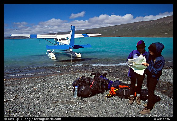 Backpackers dropped off by floatplane on Lake Turquoise orient themselves on the map. Lake Clark National Park, Alaska (color)