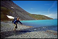 Jumping over a small stream next to Lake Turquoise. Lake Clark National Park, Alaska