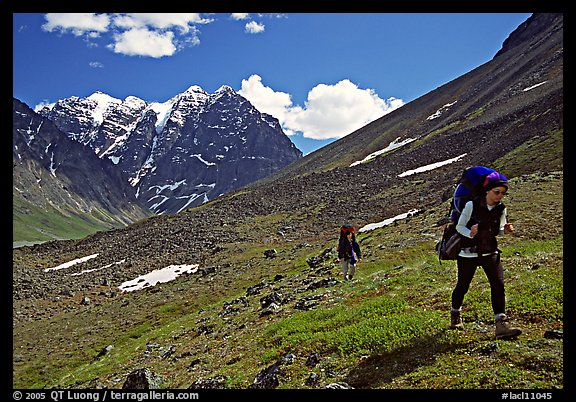 Backpackers walking on a slope. Lake Clark National Park, Alaska (color)