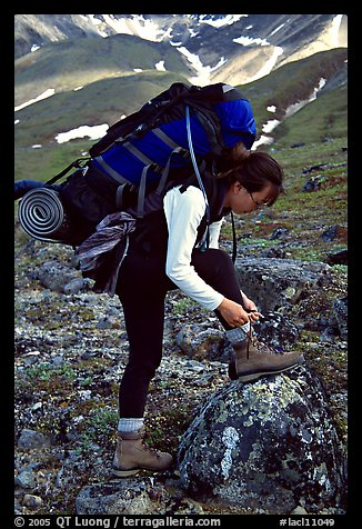 Woman backpacker with a large backpack tying up her shoelaces. Lake Clark National Park, Alaska (color)