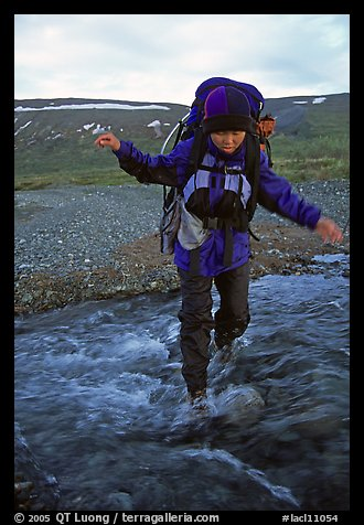 Backpacker balancing herself while crossing a stream. Lake Clark National Park, Alaska