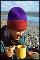 Backpacker drinking from a cup, with mosquitoes on her hat. Lake Clark National Park, Alaska (color)