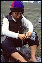 Woman backpacker drying socks after a stream crossing. Lake Clark National Park, Alaska (color)