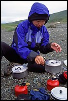 Backpacker cooks meal on gas campstove. Lake Clark National Park, Alaska (color)
