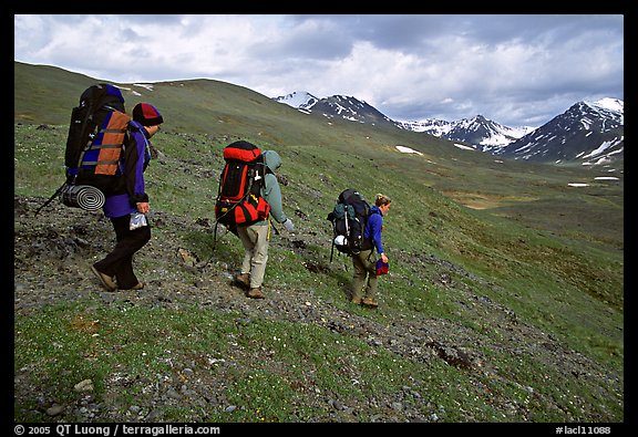 Backpackers with big packs going down a slope. Lake Clark National Park, Alaska