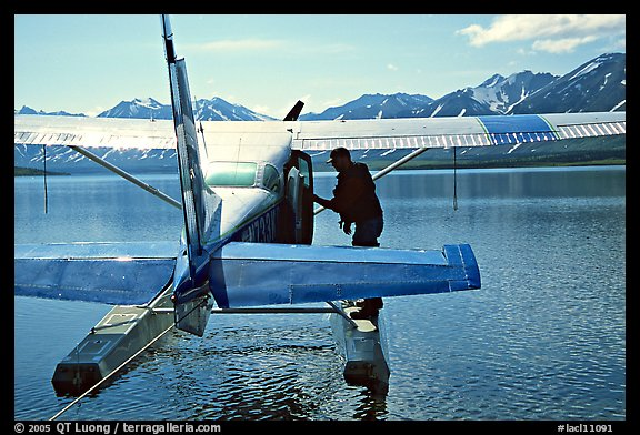 Pilot standing on floats of Floatplane, Twin Lakes. Lake Clark National Park, Alaska (color)