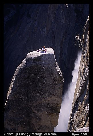 Climber resting on top of Lost Arrow spire with Yosemite Falls behind. Yosemite National Park, California (color)