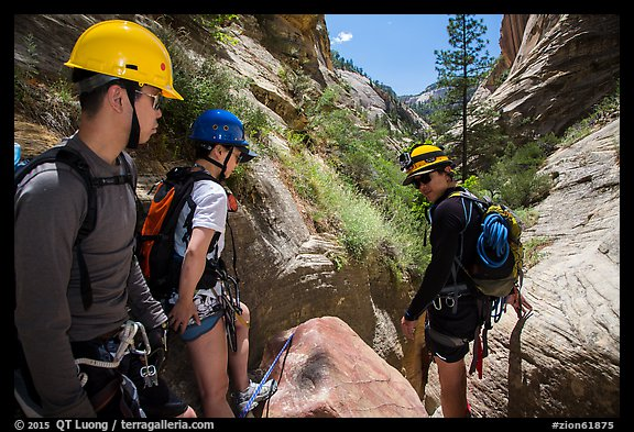 Hikers preparing to pass obstacle with ropes in Mystery Canyon. Zion National Park, Utah (color)