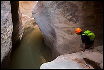 Canyoneer looks at water-filled pool. Zion National Park, Utah ( color)