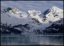 Coastal mountains with glacier dropping into icy fjord. Glacier Bay National Park, Alaska, USA.