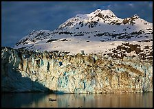 Face of Lamplugh Glacier illuminated by the sun on cloudy day. Glacier Bay National Park, Alaska, USA.