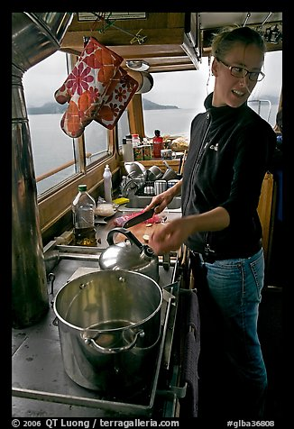Chef cooking aboard small boat. Glacier Bay National Park, Alaska, USA.