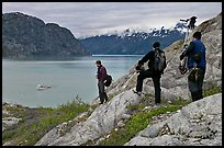Film crew carrying a motion picture camera down rocky slopes. Glacier Bay National Park ( color)