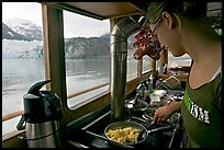 Woman prepares breakfast eggs aboard small tour boat, with glacier in view. Glacier Bay National Park, Alaska, USA. (color)