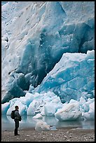 Hiker looking at ice wall at the terminus of Reid Glacier. Glacier Bay National Park, Alaska, USA. (color)