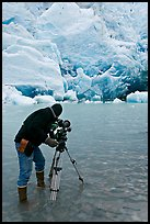 Cameraman standing in water with camera and tripod filming Reid Glacier. Glacier Bay National Park, Alaska, USA. (color)