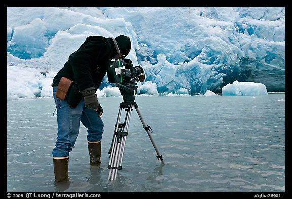 Cameraman standing in water at the base of Reid Glacier. Glacier Bay National Park (color)