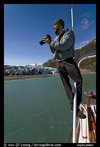 Photographer perched on boat in Reid Inlet. Glacier Bay National Park (color)