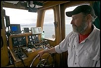 Captain steering boat with navigation instruments. Glacier Bay National Park, Alaska, USA. (color)