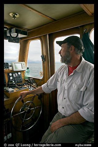 Captain steering boat using navigation instruments. Glacier Bay National Park (color)