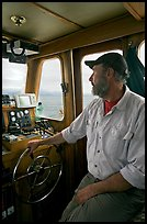 Captain steering boat using navigation instruments. Glacier Bay National Park, Alaska, USA. (color)