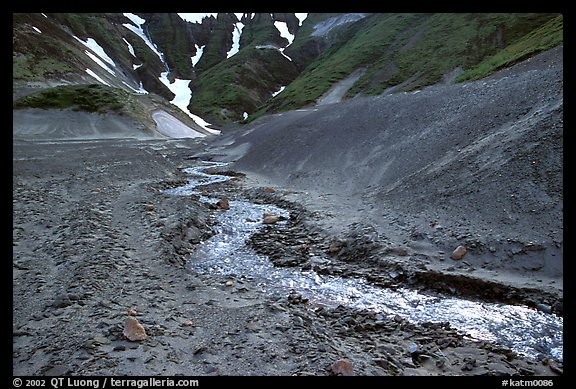 Stream flows from verdant hills into  barren valley floor. Katmai National Park (color)