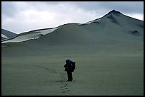 Backpacker leaves the Baked mountain behind, Valley of Ten Thousand smokes. Katmai National Park, Alaska