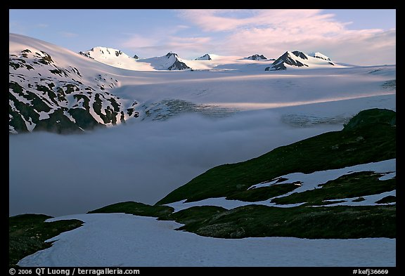 Low clouds, partly melted snow cover, and mountains. Kenai Fjords National Park, Alaska, USA.