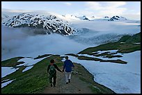 Couple hiking down Harding Icefied trail, late afternoon. Kenai Fjords National Park, Alaska, USA. (color)