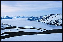 Dark bands of freshly uncovered terrain, snow, and low clouds, dusk. Kenai Fjords National Park, Alaska, USA. (color)