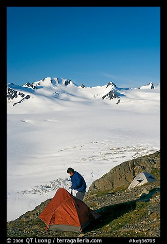Camper exiting tent above the Harding ice field. Kenai Fjords National Park, Alaska, USA.