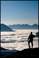 Man above a sea of clouds. Kenai Fjords National Park, Alaska, USA.