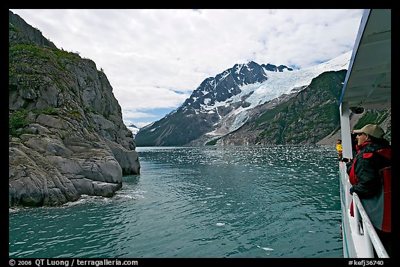 Passenger on small tour boat, island and glacier, Northwestern Fjord. Kenai Fjords National Park (color)