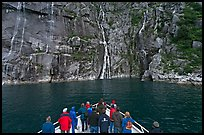 Waterfall viewing from deck of tour boat, Cataract Cove. Kenai Fjords National Park, Alaska, USA. (color)