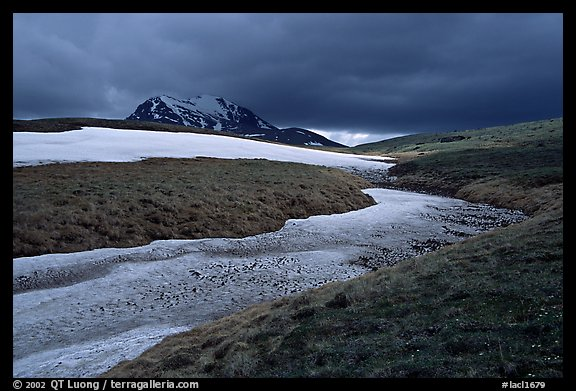 Snow nevesand mountains under dark storm clouds. Lake Clark National Park (color)