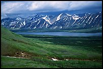 Verdant tundra, lake, and snowy mountains under clouds. Lake Clark National Park, Alaska, USA.
