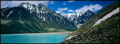 Rugged mountains rising above lake with turquoise waters. Lake Clark National Park (Panoramic color)