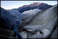 Root Glacier, glacial stream, and mountains at dusk. Wrangell-St Elias National Park, Alaska, USA.