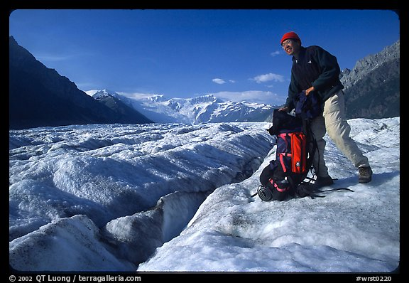 Hiker reaching into backpack on Root glacier. Wrangell-St Elias National Park (color)