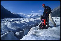 Hiker reaching into backpack on Root glacier. Wrangell-St Elias National Park ( color)