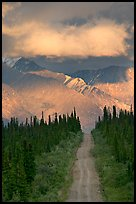 Road leading to mountains and clould lit by sunset light. Wrangell-St Elias National Park, Alaska, USA.