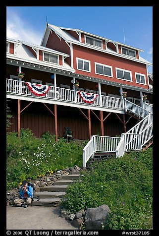 Hiker sitting on steps of Kennicott Lodge. Wrangell-St Elias National Park (color)
