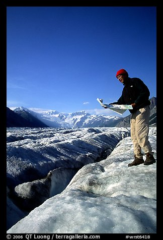 Hiker checks map on Root Glacier. Wrangell-St Elias National Park (color)
