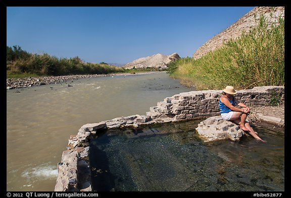 Tourist sitting in hot springs next to river. Big Bend National Park (color)